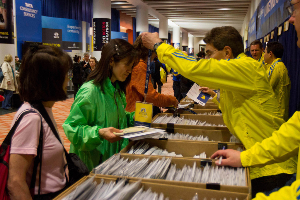 Shinobu Sugiyama, center, from Tokyo, picks up her first Boston Marathon runner's passport. (Xiaolu Liu/BU News Service)