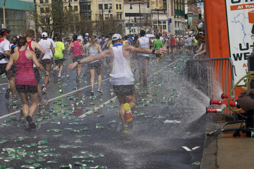 Runners pass through sprinklers and discarded cups at last year's marathon. (Emily Zendt/BU News Service)