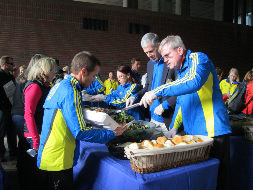 Boston Chief of Public Property Michael Galvin (right) serves food to runners outside City Hall on Sunday evening during the annual pre-marathon pasta dinner. (Lisa Kashinsky/BU News Service)