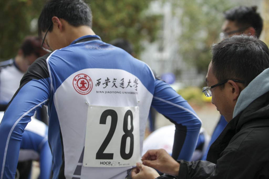 CAMBRIDGE MA – Oct. 18, Yan Gao, the deputy coach of Xi'an Jiaotong University Rowing Club, helps one athlete putting his number tag on the uniform which has their University's name and logo on the back. With an hour left before competing in the 51st Head of the Charles Rowing Regatta, competitors are doing the final preparation for the game. Photo by Chenyao