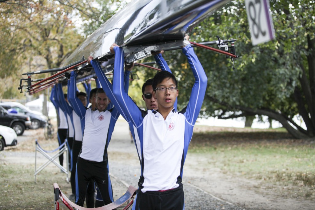 "CAMBRIDGE MA – Oct. 18 2015 - Xi'an Jiaotong University Rowing Club members lift the rowing boat over their heads, moving towards their launching point, the dock of the Riverside Boat House. "" We are the sixth generation of XJURC, the fastest-growing team and best-score keeper among all the generations,"" Said Zhiping Wang (not shown,) the captain of the team. (Photo by Chenyao Xu/BUNS)"