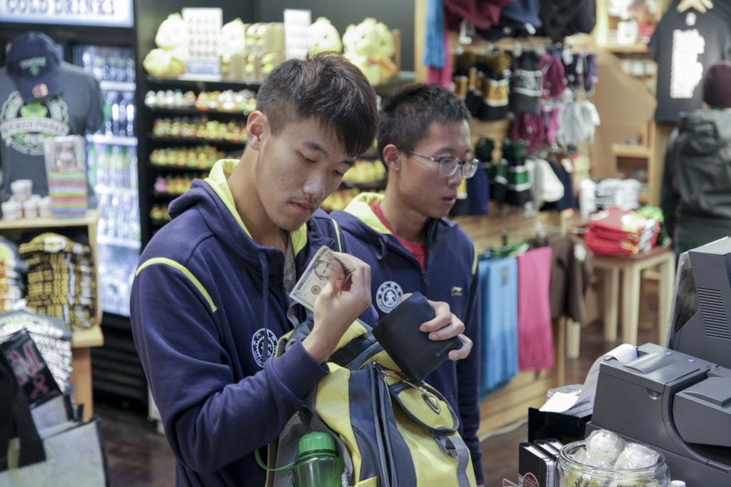CAMBRIDGE MA – Oct. 17, after watching the 51st Head of the Charles Rowing Regatta in the morning, Zhiping Wang, left, the captain of Xi'an Jiaotong University Rowing Club is buying souvenirs with his team member, Yuankai Zhang, right, in a shop near Harvard University. It's the first time for most of the team members visiting the U.S. and they will leave on Oct. 19 so that they spend all their spare time walking around the city and buying knick-knacks. Photo by Chenyao