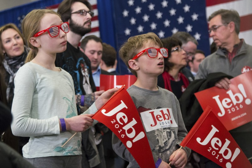 Manchester, NH, 9th Feb 2016: Claire, 11, and Theodore, 8, Kraemer react to the New Hampshire primary results at the Jeb Bush rally Tuesday night. The children, both Bedford, New Hampshire residents, waved their flags in support of their candidate's fourth place finish. (Photo by: Kyra Louie/BUNS)