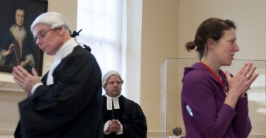 """BOSTON, March 5th, 2016:  Left to right: Actors Ed Hurley, Mike LePage listen to Kathy Mulvaney, educator at Old State House as she explains the audience roles, in the interactive play """"Trial of the Century"""". The play is a part of the Old State House's program in commemoration of the Boston Massacre. (Marwa Morgan/BUNS)"""