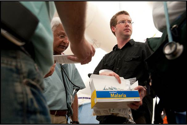 Doctors passing out rapid malaria tests