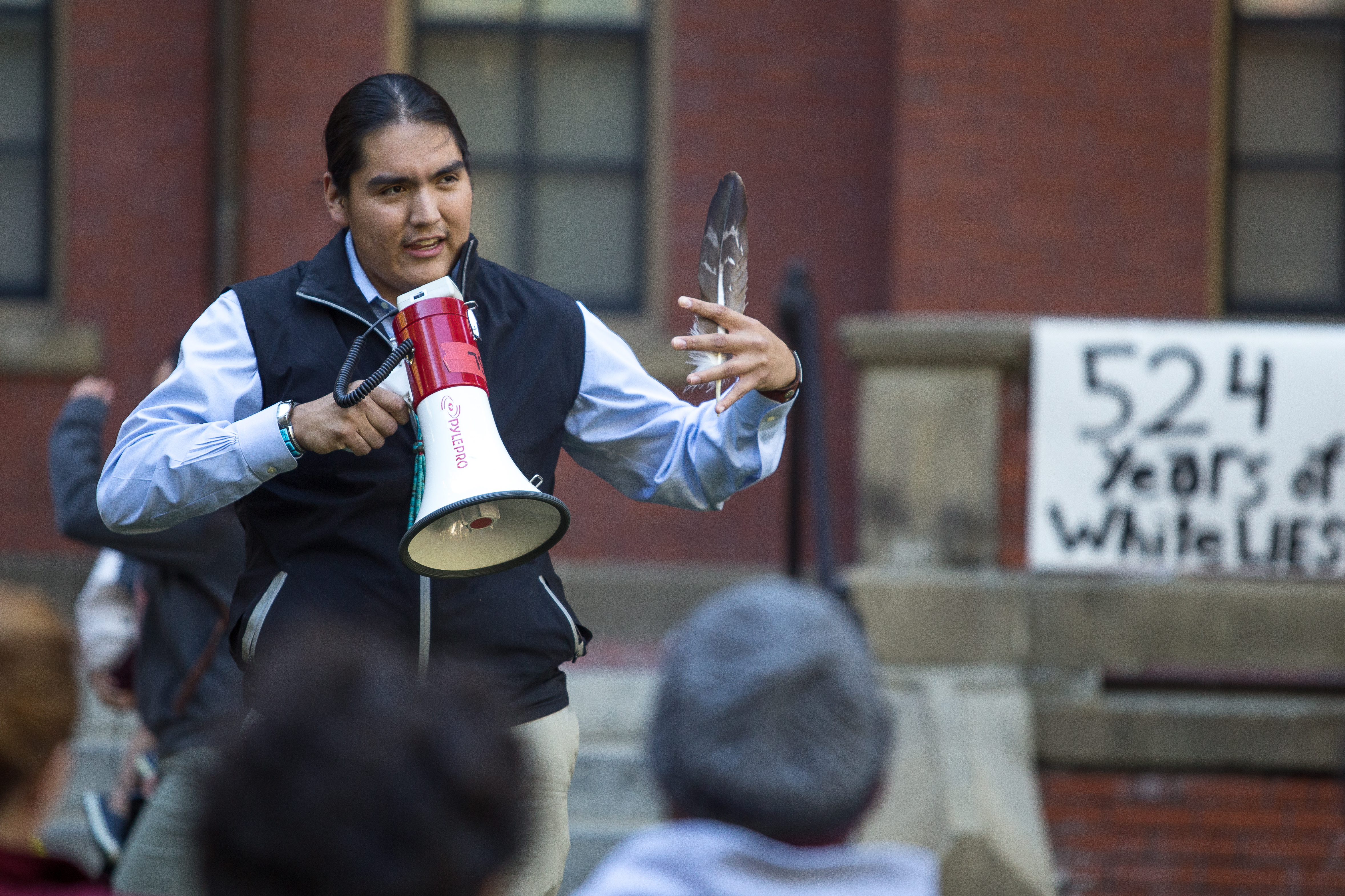 Damon Clark, a member of Native Americans at Harvard College, welcomes attendees to an Indigenous Peoples' Day celebration at Harvard University on Monday evening. More than 100 people gathered in Harvard Yard for conversation and cultural performances. Photo by Alexandra Wimley/BU News Service