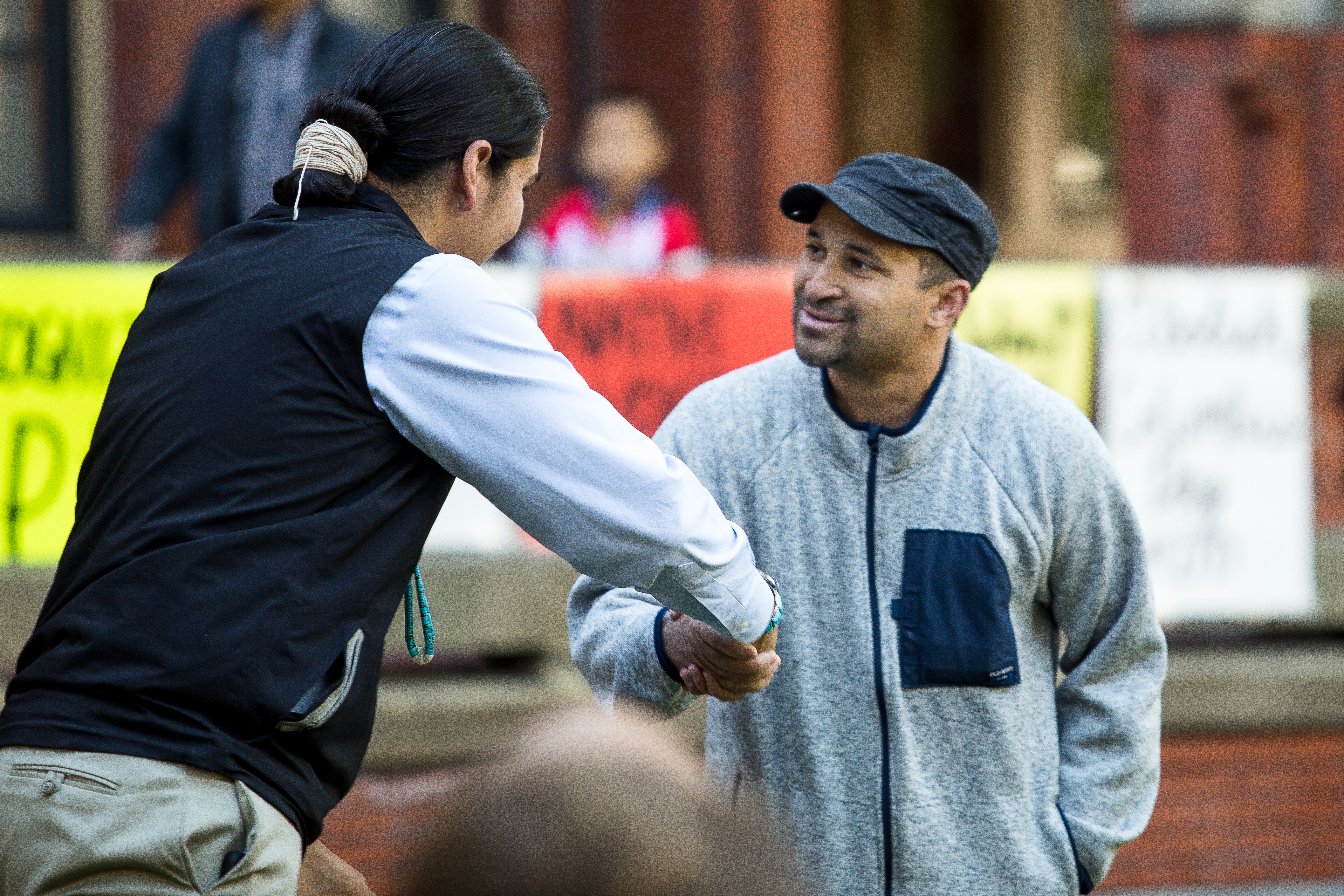 Clark (left) greets William Ridgley, a representative from Local 26, the union representing food service workers at Harvard University. The strikers paused their nearby demonstration to show support for the Indigenous Peoples' Day celebration. Photo by Alexandra Wimley/BU News Service.