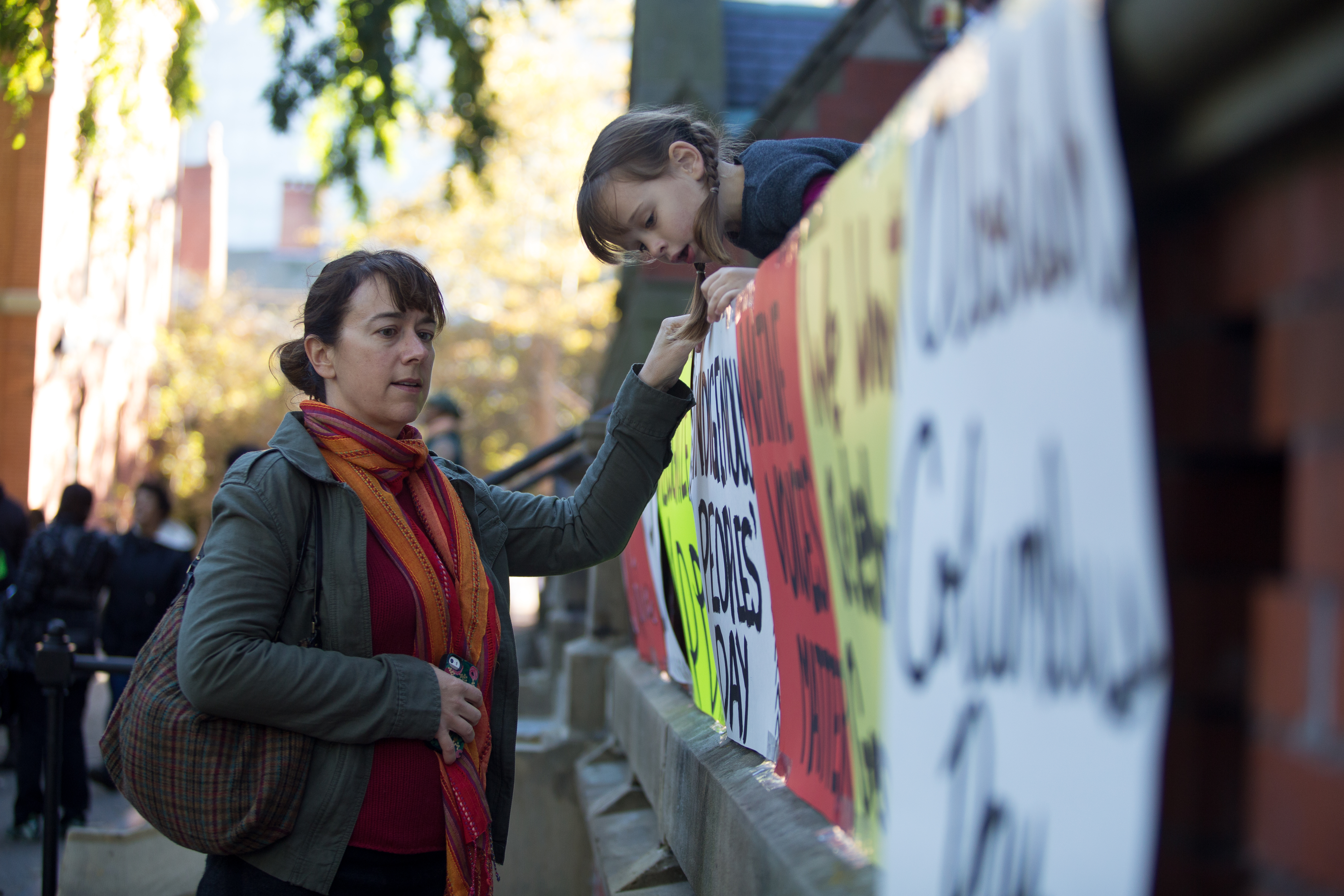 "Julie Bowden (left) tells Josie Grudzinski, 4, what each sign says in Harvard Yard. Signs said things like ""Abolish Columbus Day"" and ""We Won't Support Genocide"". Photo by Alexandra Wimley/BUNS"