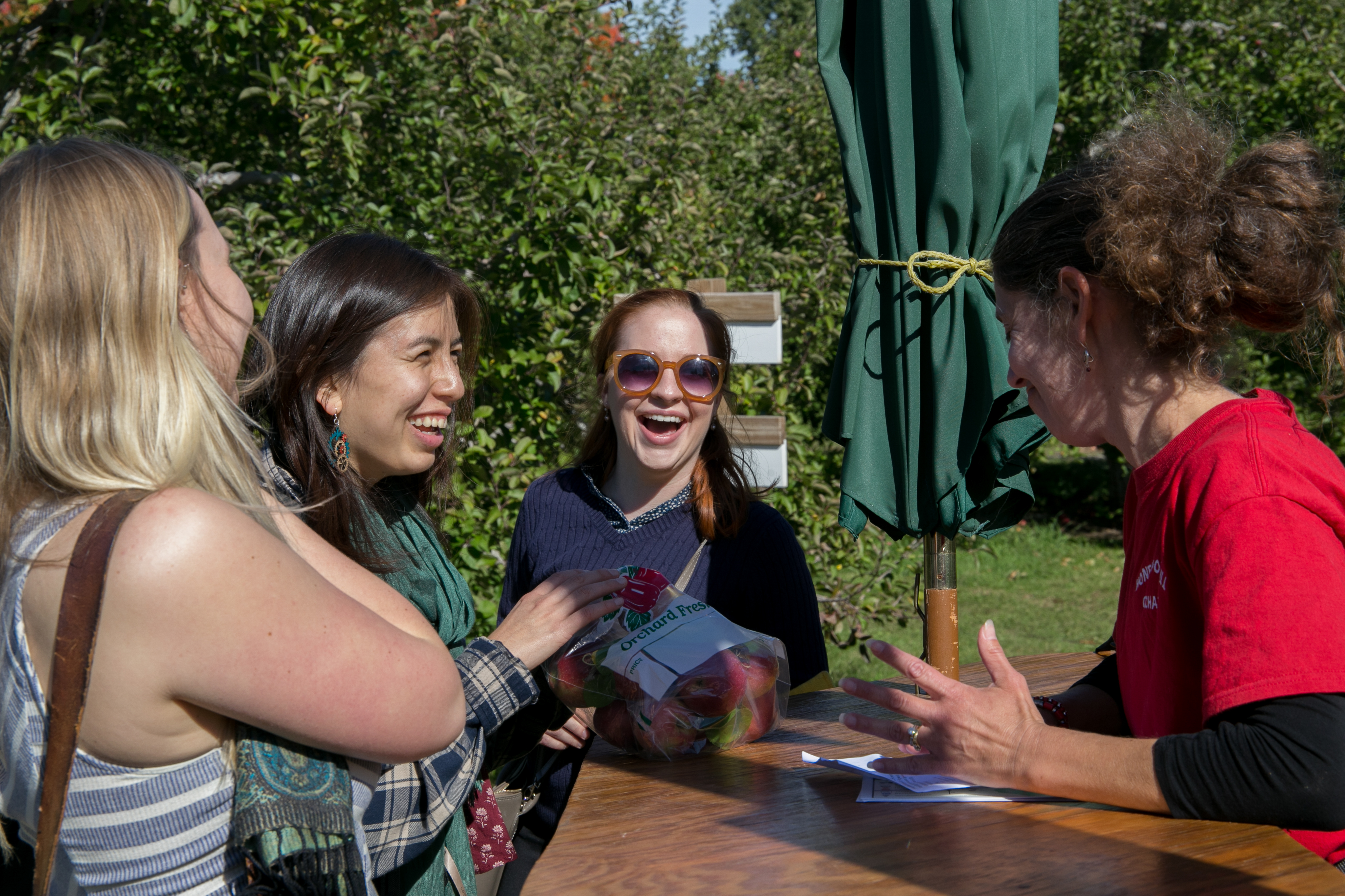(From left) Grace Wingler, 21, Anais Azul, 21, and Ellen Leightcap 21, speak with Karen Axelrod, who works at Honey Pot Hill Orchards. Photo by Silvia Mazzocchin/BU News Service