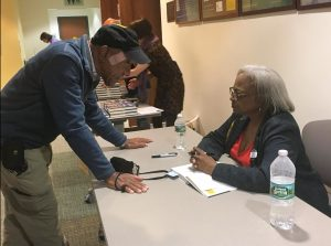 Carol Anderson signs copies of her book and talks about elections with attendees after her discussion at the Public Library of Brookline. Sept. 11. Photo by Noor Adatia / BU News Service.