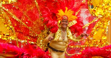 Member of the Caribbean Carnival Association displays her costume at the Columbus Day Parade in East Boston, on Sunday, Oct. 7. Photo by Flaviana Sandoval / BU News Service